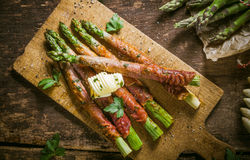 Asparagus Wrapped in Bacon with Curl of Butter Stock Images