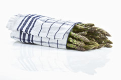 Asparagus wrapped in cloth on white background Stock Image