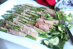 Asparagus wrapped with prosciutto. On a plate Royalty Free Stock Photos