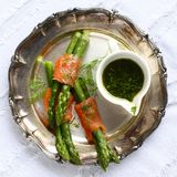 Asparagus wrapped in smoked salmon with dill sauce on metal plate.  Stock Photos