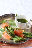Asparagus wrapped in smoked salmon with dill sauce on metal plate.  Royalty Free Stock Image