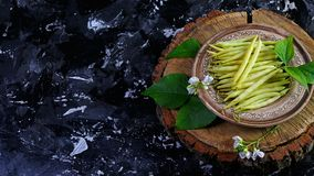 Asparagus yellow beans on a clay plate, on wooden stump, dark background. Food recipe on wooden background. Flat top view from abo stock images