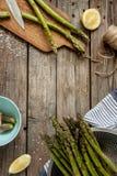 Aspargo na cozinha rural - preparando-se para cozinhar na tabela de madeira do vintage Imagem de Stock