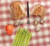 Aspargo, pão, e ovos de codorniz na toalha de mesa quadriculado Imagens de Stock