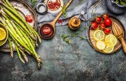 Aspargo saboroso que cozinha com tomates, limão e tempero, preparação na mesa de cozinha rústica com colher de madeira, vista sup Imagens de Stock Royalty Free