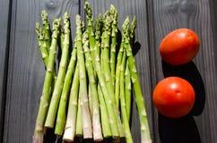 Aspargus y comida de los tomates cruda Imágenes de archivo libres de regalías