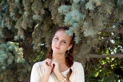 Aspecto de la muchacha contra un abeto Fotos de archivo libres de regalías