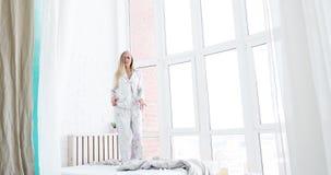 Aspecto femenino europeo espléndido, danza en la cama en buen humor, vida feliz y vibrante del nuevo día Mujer que lleva de largo almacen de video