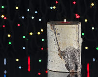 An Aspen Log Candle and Christmas Lights Stock Photo