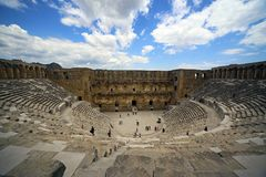 Aspendos Theater, Antalya, Turkey. Tourist in Aspendos Theater amphitheater in Antalya, Turkey against blue skies on sunny day Stock Images