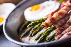 Asperge Asperge en broodjesbacon Geroosterde asperge met gerold bacon en gebraden ei Gebraden oud panhoogtepunt van gerold bacon  stock afbeeldingen
