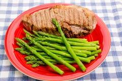 Asperge de plat rouge avec le bifteck Photos stock