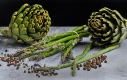 Asperge et artichauts avec des herbes photographie stock