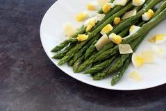 Asperge verte avec des copeaux de parmesan et d'oeufs coupés Photo stock
