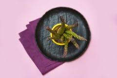Asperge verte fraîche sur le plat en céramique noir, serviette de toile pourpre sur le fond rose photo libre de droits