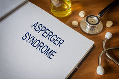 Asperger syndrome written on book with tablets Stock Photo