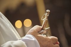 The asperges in the hands of the priest stock images