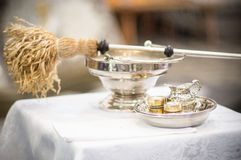 Aspergillum and holy water. An aspergillum and holy water pitcher with other church ware Stock Image