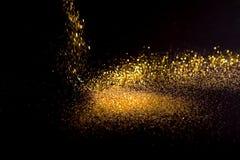 Asperje el polvo de oro en un fondo negro Foto de archivo libre de regalías