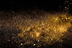 Asperje el polvo de oro en un fondo negro Fotografía de archivo