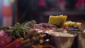 Asperje la sal al plato delicioso de la carne con maíz, romero y salsas Cierre para arriba metrajes