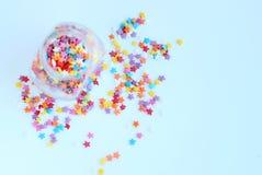 Aspersión coloreada brillante de la confitería de estrellas en un tarro de cristal en un fondo ligero Foco suave, falta de defini fotografía de archivo