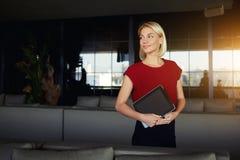 Aspettare femminile intelligente sorridente del proprietario di ristorante clienti mentre tiene il cuscinetto di tocco con la cop Fotografie Stock Libere da Diritti
