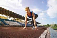 Aspetti per andare atleta biondo femminile in camicia blu e ghette sulla linea di partenza di pista dello stadio, preparante per  Immagini Stock Libere da Diritti