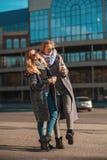 Aspetti per comperare! Un ritratto di due belle donne in cappotti ed occhiali da sole che bevono caffè mentre camminare all'apert immagini stock