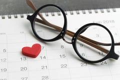 Aspetti per il concetto del giorno del ` s del biglietto di S. Valentino con gli occhiali ed adorabile rosso Fotografia Stock