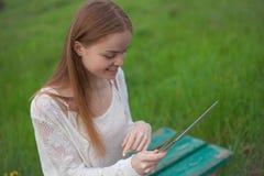 Aspetto europeo della ragazza felice che si siede sul banco con il computer portatile Fotografie Stock Libere da Diritti
