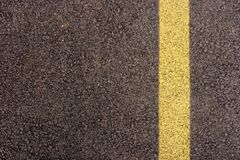 Asphalt. Texture closeup of an asphalt road with painted yellow line on the side Royalty Free Stock Photos