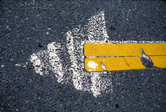 Asphalt arrow. Painted arrow on asphalt roadway in white and yellow Stock Images