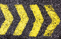 Asphalt arrow yellow sign Stock Images