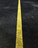 Yellow line on asphalt Royalty Free Stock Images