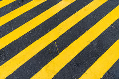 Asphalt Background with diagonal black and yellow warning stripe Stock Photos
