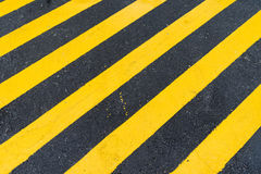 Asphalt Background with diagonal black and yellow warning stripe Royalty Free Stock Photos