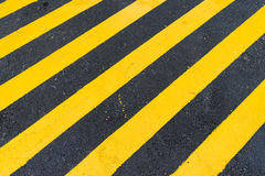 Asphalt Background mit diagonalem schwarzem und gelbem warnendem Streifen Lizenzfreies Stockfoto