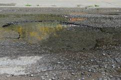 Asphalt bad. Pits and puddles on a not even asphalt, water hurries on a road, but not on a ditch Stock Photos