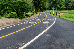 Asphalt bicycle road with yellow line. And bicycle lane sign Stock Photos