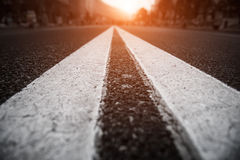 Asphalt city road with white lines ahead and the sunset. Royalty Free Stock Photography