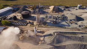 Asphalt-concrete plant with running excavators and bulldozers. aerial view. The plant serves the needs of road construction stock footage