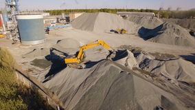 Asphalt-concrete plant with running excavators and bulldozers. aerial view. The plant serves the needs of road construction stock video footage