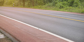 Asphalt/concrete road around forest. Royalty Free Stock Photography
