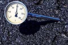 Thermometer in hot aspahlt mix Royalty Free Stock Image