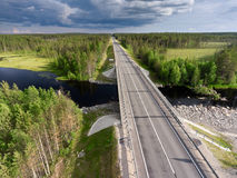 Asphalt country road across small river. Bridge over water and swamps. Karelia, Russia royalty free stock photo
