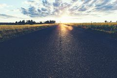 Asphalt country road, a grass field and sunset. stock photos