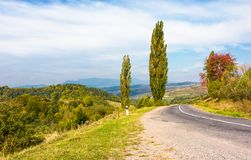 Asphalt country road through hills with trees. Lovely autumn weather in mountains Stock Photo