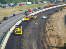 Asphalt crew. Workers laying asphalt in freeway construction zone Stock Image