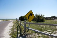 An asphalt curved road along the beach at Dauphin Island, Alabama USA. An asphalt curved road with sand on it winding along the coastal shoreline of Dauphin Royalty Free Stock Image
